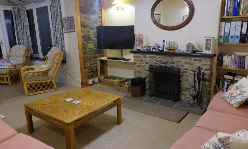 The comfortably furnished lounge with flatscreen TV, DVD and open fireplace